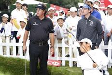 U.S. golfer Phil Mickelson (L) stands as he explains how to play golf to children in Shanghai October 30, 2013. REUTER/Aly Song