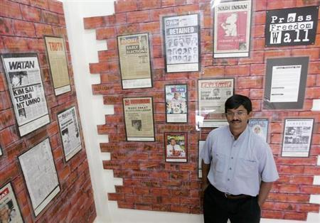 Malaysiakini.com Chief Executive Officer (CEO) Premesh Chandran poses in front of the ''press freedom'' wall at his office in Kuala Lumpur May 23, 2006. REUTERS/Zainal Abd Halim/Files
