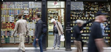 A woman leaves a food shop as people walk past it in central Barcelona October 29, 2013. REUTERS/Albert Gea