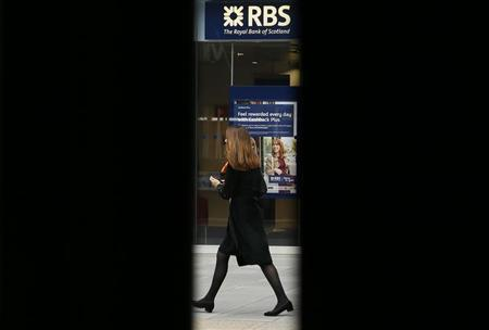 A woman is seen through scaffolding as she walks past a branch of the Royal Bank of Scotland in London September 17, 2013. REUTERS/Stefan Wermuth