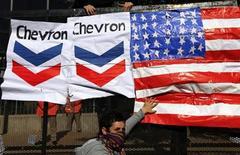 Демонстрант в маске притрагивается к американскому флагу рядом с логотипом Chevron на акции протеста в Буэнос-Айресе 16 июля 2013 года. Украина надеется подписать с американской соглашение о добыче сланцевого газа, за счет которого рассчитывает снизить зависимость от российского Газпрома. REUTERS/Marcos Brindicci