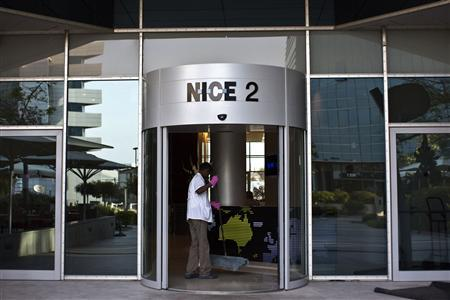 A worker cleans beneath the logo of Nice Systems at the entrance of its headquarters in the Israeli city of Raanana, near Tel Aviv October 2, 2013. REUTERS/Nir Elias