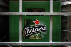 A plastic container with empty bottles of Heineken beers are pictured among beer kegs outside a restaurant in Singapore August 29, 2012. REUTERS/Tim Chong