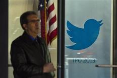 Homem passa por cartaz do Twitter ao deicar a sede do banco JP Morgan, em Nova York. Investidores institucionais que se reuniram com o Twitter nesta semana mostraram-se otimistas com a oferta pública inicial de ações (IPO, na sigla em inglês) e que veem poucos sinais de exuberância irracional como a que precedeu a estreia conturbada do Facebook em 2012. 25/10/2013 REUTERS/Eduardo