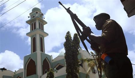 A police officer holds his position outside the Masjid Mussa mosque during an operation to to suppress demonstrators reacting to the killing of an Islamic cleric at Kenya's coastal city of Mombasa October 4, 2013. REUTERS/Joseph Okanga