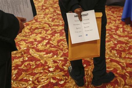 A man holds a pamphlet handed out by a recruiter while attending a job fair in New York, June 11, 2013. REUTERS/Lucas Jackson
