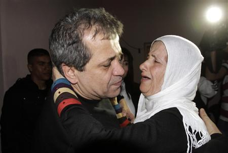 Released Palestinian prisoner Moayyad Hajji, 46, who was arrested in 1992, hugs his sister upon his arrival at his family's house in the West Bank village of Burqa near Nablus October 30, 2013. REUTERS/Abed Omar Qusini