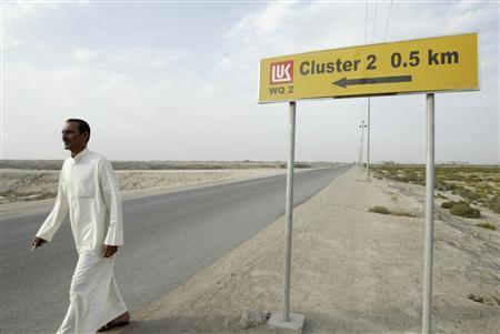 A man walks past a sign for ''Lukoil'' in al-Toraba area near oilfield of West Qurna-2 in Basra, 420 km (261 miles) southeast of Baghdad, October 26, 2013. REUTERS/Essam Al-Sudani