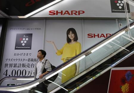 A man rides an escalator past Sharp Corp's advertisements at an electronics retail store in Tokyo October 31, 2013. REUTERS/Toru Hanai