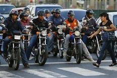 Motorcyclists wait for the traffic lights to change at a road junction in Caracas October 25, 2013. REUTERS/Jorge Silva