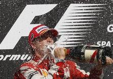Ferrari GP Formula One driver Kimi Raikkonen of Finland drinks champagne on the podium after winning the Belgian F1 Grand Prix in Spa Francorchamps August 30, 2009. REUTERS/Thierry Roge