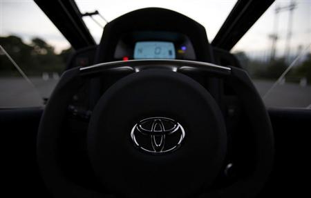 A logo of Toyota is seen on the steering wheel of Toyota's ultra-compact tandem two-seater electric vehicle i-ROAD during the Toyota Advanced Technologies media briefing in Tokyo October 10, 2013. REUTERS/Yuya Shino