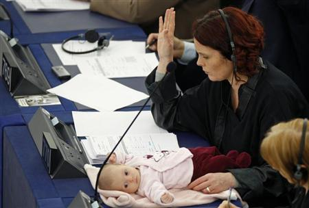 Denmark's member of the European Parliament Hanne Dahl votes as she attends with her baby a voting session at the European Parliament in Strasbourg March 26, 2009. REUTERS/Vincent Kessler