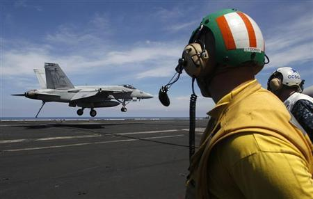 A U.S. Navy F/A 18 Hornet aircraft prepares its tailhook to catch an arresting wire in a landing maneuver during a tour of the USS Nimitz aircraft carrier on patrol in the South China Sea May 23, 2013. REUTERS/Edgar Su