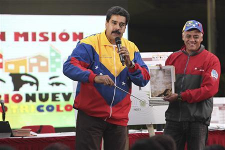 Venezuela's President Nicolas Maduro (L) shows a picture of a metro tunnel wall with an image which he says is the face of late President Hugo Chavez, in Caracas October 30, 2013. REUTERS/Miraflores Palace/ Handout via Reuters