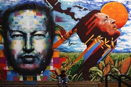 A man sits next to a mural depecting the late Venezuelan President Hugo Chavez in downtown Caracas September 23, 2013. REUTERS/Jorge Silva/Files