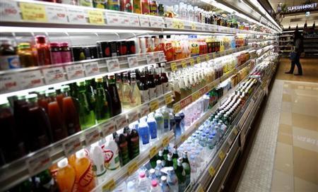 A woman looks at drinks at a supermarket at Ginza shopping district in Tokyo October 31, 2013. REUTERS/Yuya Shino