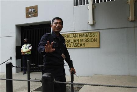 A security personnel raises his hand in an attempt to stop the media from taking pictures in front of the Australian Embassy gate in Jakarta November 1, 2013. REUTERS/Beawiharta