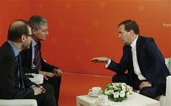 Russia's Prime Minister Dmitry Medvedev (R) speaks with Stephen Adler (front L), Editor In Chief, Reuters News, and Timothy Heritage, Bureau Chief, CIS, during an interview with Reuters in Moscow, October 31, 2013. REUTERS/Grigory Dukor