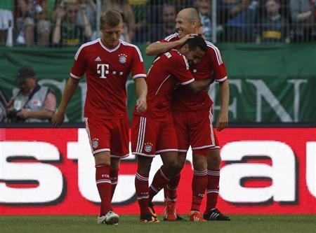 Bayern Munich's Thiago of Spain (C) celebrates his goal against Borussia Moenchengladbach with Arjen Robben (R) and Toni Kroos during their Telekom Cup soccer match in Moenchengladbach July 21, 2013. REUTERS/Wolfgang Rattay