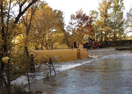 A school bus flipped on its side after it slid off a road into a creek is shown in this photo taken by Butler County Sheriff Kelly Herzet in Butler County, Kansas on October 31, 2013. REUTERS/Butler County Sheriff's Office/Handout via Reuters