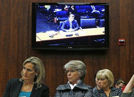Audience members listen to Illinois Assistant Attorney General and Director of Public Policy Erik Jones (on screen) testify at an Illinois House of Representatives' adoption reform committee in Chicago, October 29, 2013. REUTERS/Jim Young