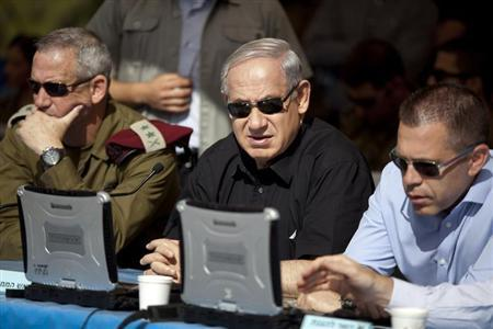 Israeli Prime Minister Benjamin Netanyahu (C) sits next to armed forces chief Major-General Benny Gantz (L) and Gilad Erdan, minister of communications and home front protection, during a drill simulating a chemical rocket attack in Jerusalem May 29, 2013. REUTERS/Abir Sultan/Pool