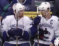 Vancouver Canucks left wing Daniel Sedin (L) talks with his twin brother Henrik while on the bench during Game 4 of their NHL Western Conference Hockey quarter-final playoff against the Los Angeles Kings in Los Angeles, California April 18, 2012. REUTERS/Danny Moloshok