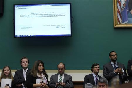 Staff members working for Republican U.S. congressmen look on under an image of the Healthcare.gov website, which is currently down, as U.S. Secretary of Health and Human Services Kathleen Sebelius testifies before a House Energy and Commerce Committee hearing on the failures of the Affordable Care Act enrolment website on Capitol Hill in Washington, October 30, 2013. REUTERS/Jason Reed