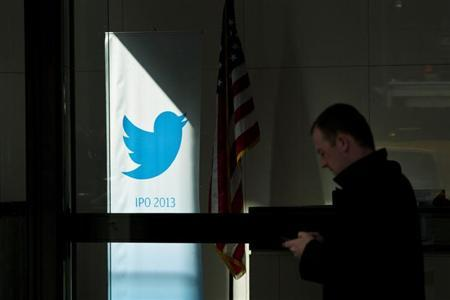 A man walks past a Twitter banner while leaving JP Morgan headquarters, before the firm's IPO in New York, October 25, 2013. REUTERS/Eduardo Munoz