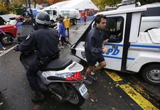 A runner makes his way past New York City Police (NYPD) officers near the finish line of the New York City Marathon in New York's Central Park November 1, 2013. REUTERS/Mike Segar