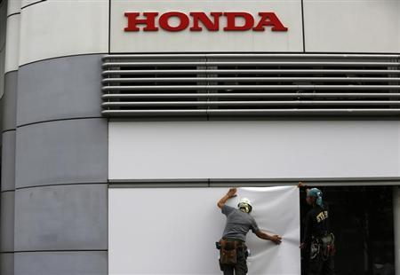 Workers stand under the logo of Honda Motor Co. outside the company's headquarters in Tokyo October 30, 2013. REUTERS/Issei Kato