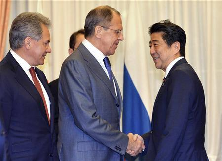 Russia's Foreign Minister Sergey Lavrov (2nd L) and Defence Minister Sergei Shoigu (L) shakes hands with Japan's Prime Minister Shinzo Abe at the start of their meeting at the prime minister's residence in Tokyo November 2, 2013. REUTERS/Yoshikazu Tsuno/Pool