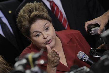 Brazil's President Dilma Rousseff (C) speaks to the media after a ceremony for the new law, the Programa Mais Medicos (Program More Doctors), at the Planalto Palace in Brasilia October 22, 2013. REUTERS/Ueslei Marcelino