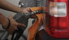 """Funcionário de posto de gasolina enche tanque na praia do Leme, no Rio de Janeiro. A presidente Dilma Rousseff negou que tenha emitido opinião a respeito de mecanismos de reajustes de preços de combustíveis, depois de reportagem publicada pelo jornal O Estado de S. Paulo neste sábado ter afirmado que a presidente avalizou a concessão de um """"gatilho"""" para reajustar os preços dos derivados de petróleo """"duas ou três vezes por ano"""". 30/03/2011 REUTERS/Ricardo Moraes"""