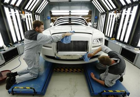 Employees Joe Don (L) and Darren Lowarson give a Rolls Royce Ghost its final finish polish at the Rolls Royce Motor Cars factory at Goodwood near Chichester in southern England April 24, 2013. REUTERS/Luke MacGregor