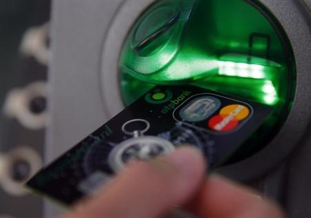 A customer performs a transaction on an ATM at a branch of Hungary's largest lender OTP Bank in central Budapest July 24, 2013. REUTERS/Laszlo Balogh