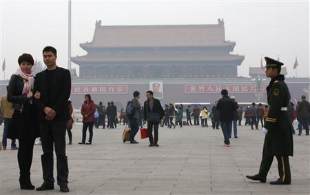 A paramilitary soldier patrols near visitors posing for souvenir pictures at Tiananmen Square in Beijing, November 1, 2013. REUTERS/Kim Kyung-Hoon