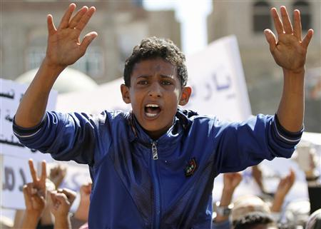 A boy shouts slogan as he sits on the back of a friend during a protest outside the home of Yemeni President Abd-Rabbu Mansour Hadi against the fighting between the Shi'ite Houthi movement and Salafi militants in the northern town of Damaj, in Sanaa, November 2, 2013. REUTERS/Mohamed al-Sayaghi