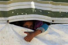 A Palestinian refugee girl from Syria peeps through a tent at Ain al-Helweh Palestinian refugee camp near the port-city of Sidon, southern Lebanon October 8, 2013. REUTERS/Ali Hashisho
