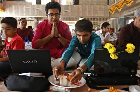 Businessmen offer prayers to Hindu gods in front of their laptops as part of a ritual to worship the Hindu deity of wealth Goddess Lakshmi on Diwali, the Indian festival of lights, in Ahmedabad November 3, 2013. REUTERS/Amit Dave