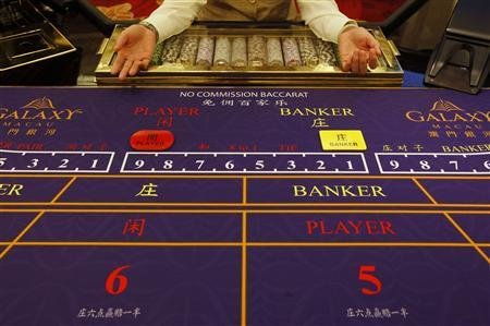 A croupier sits in front of a gaming table inside a casino in Macau in this May 15, 2011 file photo. REUTERS/Bobby Yip/Files