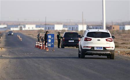 A police officer stops a car to check for identifications at a checkpoint near Lukqun town, in Xinjiang province in this October 30, 2013 file photo. REUTERS/Carlos Barria/Files