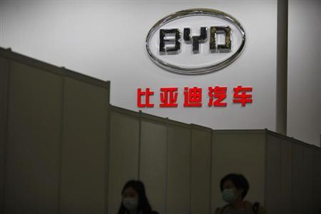 Women walk in front of the logo of Chinese car manufacturer BYD (Build Your Dreams) Auto stage before the opening of the 15th Shanghai International Automobile Industry Exhibition in Shanghai April 19, 2013. REUTERS/Aly Song