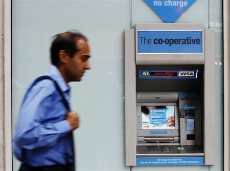 A man passes by The Co-operative Bank cash machine in London October 21, 2013. REUTERS/Luke MacGregor