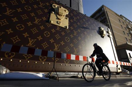A woman rides her bicycle past a construction site where a giant advertisement wall presents a Louis Vuitton trunk at a shopping centre in Warsaw April 15, 2013. REUTERS/Kacper Pempel