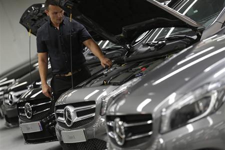An employee checks Mercedes-Benz A-class cars displayed in a dealership of German car manufacturer Daimler in Paris, July 30, 2013. REUTERS/Christian Hartmann