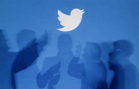 The shadows of people holding mobile phones are cast onto a backdrop projected with the Twitter logo in this illustration picture taken in Warsaw September 27, 2013. REUTERS/Kacper Pempel