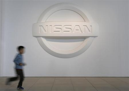 A visitor runs past the logo of Nissan Motor Co at the company's showroom in Yokohama, south of Tokyo November 1, 2013. REUTERS/Yuya Shino