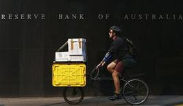 Человек проезжает мимо здание ЦБ Австралии в Сиднее 2 апреля 2013 года. Центробанк Австралии сохранил ставки на рекордно низком уровне 2,5 процента третий месяц подряд, указав на то, что прошлое смягчение политики все еще поддерживает спрос, но предупредил, что полное восстановление может быть невозможным без ослабления валюты. REUTERS/Daniel Munoz